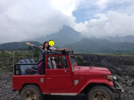 In our dashing red jeep against the backdrop of Mt. Merapi.